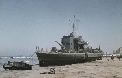 German forces move into Dunkirk hours after the evacuation of the British Expeditionary Force was completed. A beached French coastal patrol craft at low tide at Dunkirk. The ship is armed with a 75mm canon on its foredeck and probably dates from the First World War. A British Universal Carrier and a bicycle lie abandoned half buried in the sand.