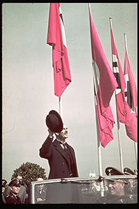 A photography of British Prime Minister Neville Chamberlain waving to spectators from an open-top car.